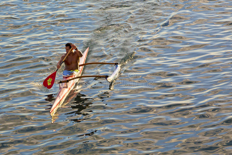 Polynesian man training on racing outrigger canoe. Papeete, Tahiti, French Polynesia - August 23, 2017: Polynesian man training on racing outrigger canoe royalty free stock photos