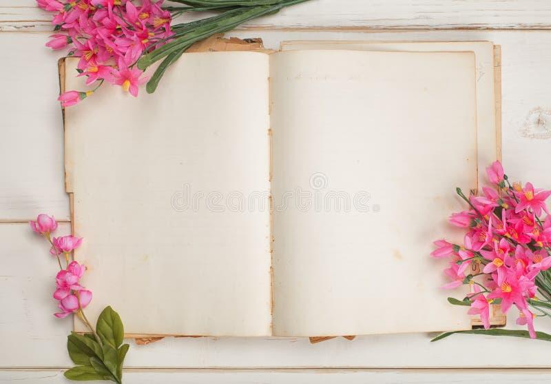 Papel aberto e vazio do jornal do vintage ou livro estacionário com as flores femininos cor-de-rosa no fundo chique gasto da tabe foto de stock