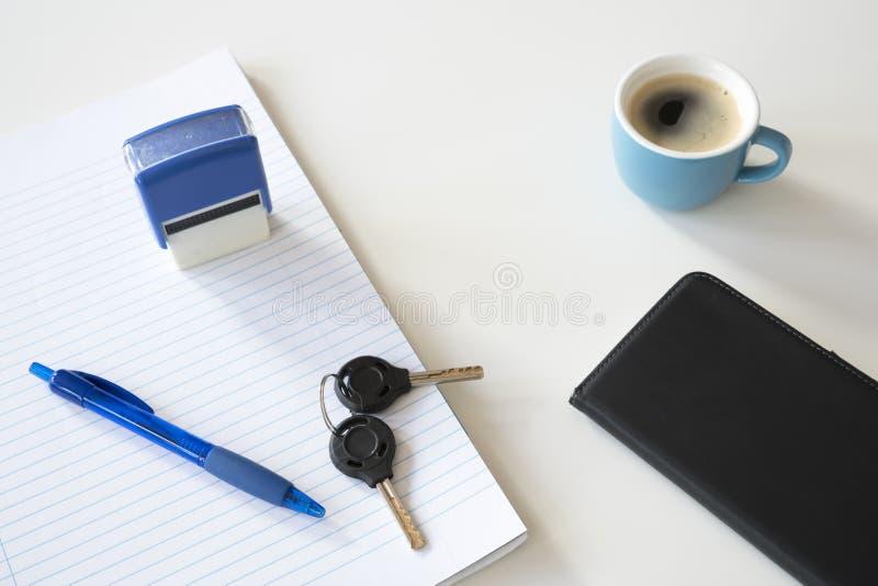 Papel alinhado com pena, selo, o smartphone e café azuis na mesa branca imagem de stock royalty free