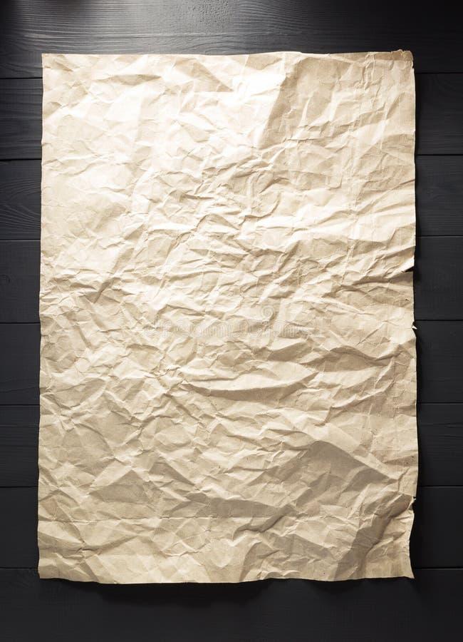 Papel arrugado en la madera imagen de archivo