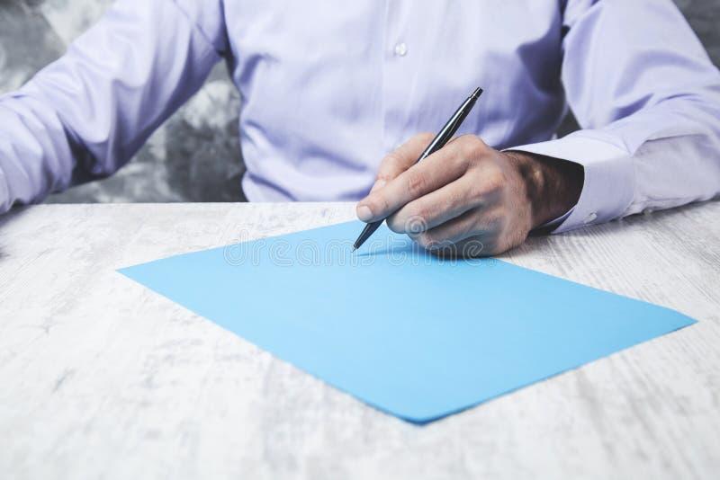 Papel azul de la mano del hombre con la pluma foto de archivo libre de regalías