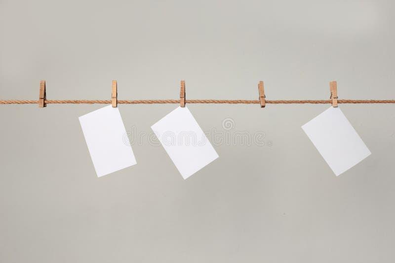 Papel blanco de la foto Colgante en una cuerda para tender la ropa con las pinzas fotografía de archivo libre de regalías