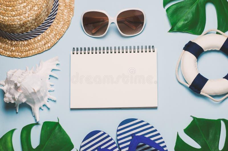 Papel blanco en blanco del cuaderno con el sombrero de paja, la concha marina, las gafas de sol, las hojas azules de la sandalia, fotos de archivo libres de regalías