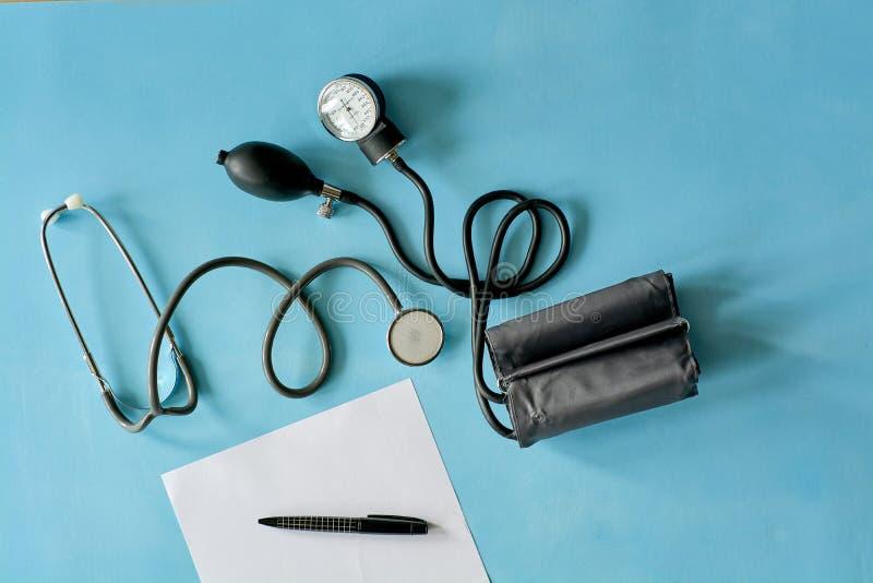 Papel branco da folha com o estetoscópio preto da pena e do phonendoscope, sphygmomanometer no fundo azul imagens de stock royalty free