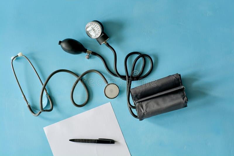 Papel branco da folha com o estetoscópio preto da pena e do phonendoscope, sphygmomanometer no fundo azul fotografia de stock royalty free