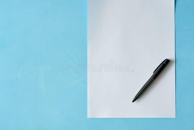 Papel branco da folha com a pena preta isoleted no claro - fundo azul fotografia de stock