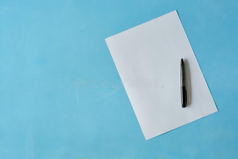 Papel branco da folha com a pena preta isoleted no claro - fundo azul fotos de stock royalty free