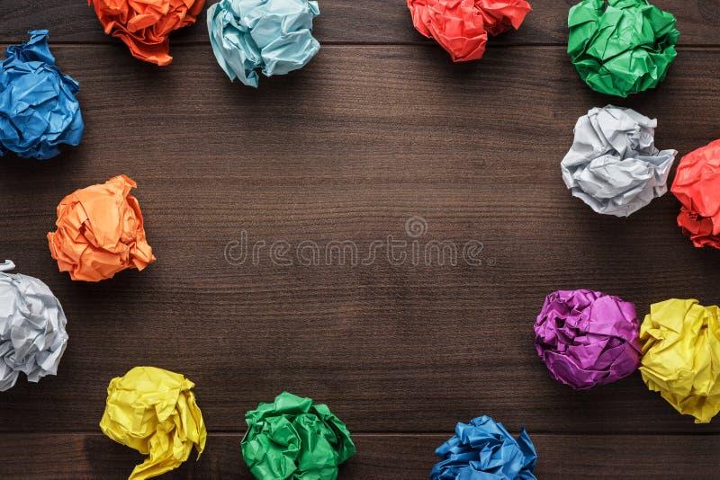 Papel colorido amarrotado no fundo de madeira fotos de stock royalty free