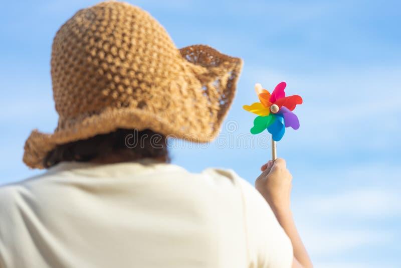 Papel colorido do moinho de vento bordado na opinião do mar da praia no dia com um fundo azul Conceito do ver?o fotografia de stock