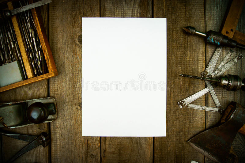 Papel com lápis e as ferramentas de funcionamento do vintage sobre foto de stock