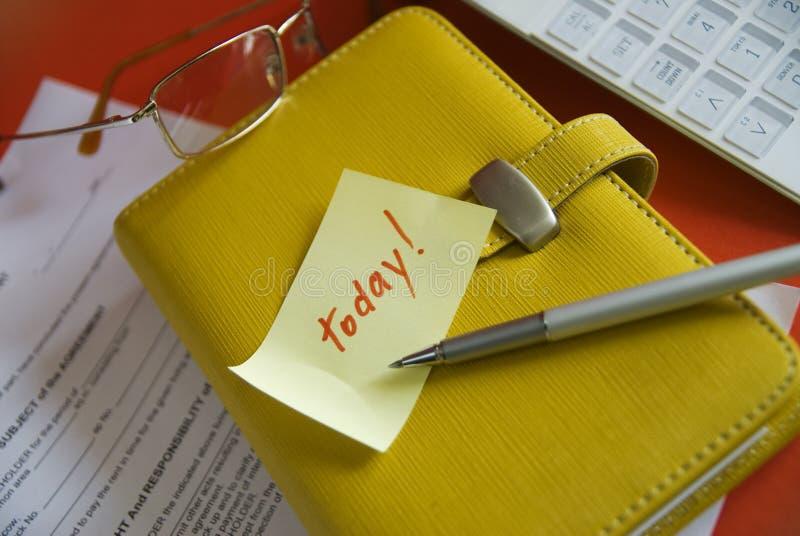 Papel com um lembrete e uns artigos de papelaria foto de stock