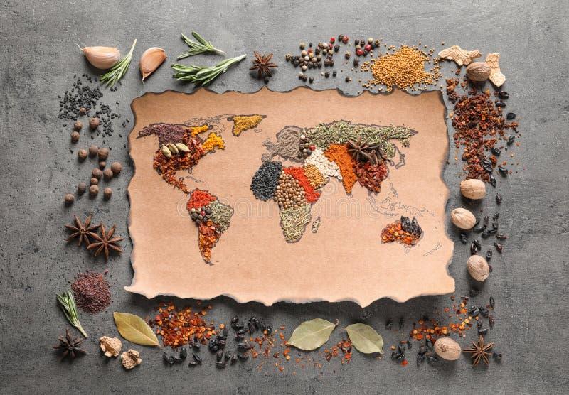 Papel con el mapa del mundo hecho de diversas especias aromáticas en fondo gris fotos de archivo