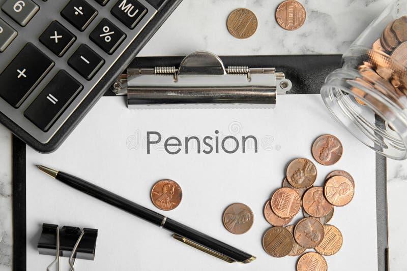 Papel con la palabra PENSIÓN, monedas, calculadora y pluma en la tabla, endecha plana foto de archivo