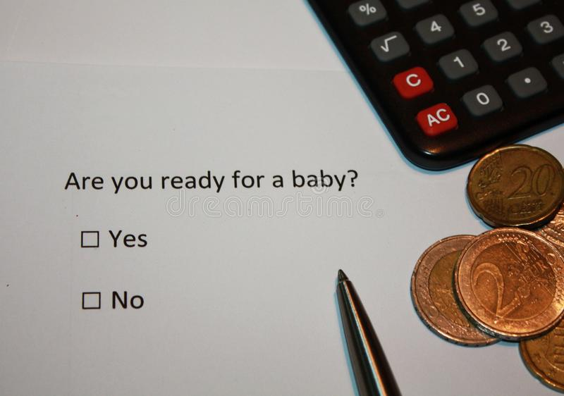 Papel con la pregunta de la encuesta: ¿Está usted listo para un bebé? Sí o ninguna caja y monedas y calculadora del euro Planeami imagen de archivo libre de regalías