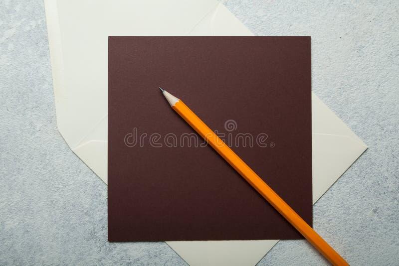 Papel con membrete en blanco y lápiz anaranjado en el fondo blanco del vintage fotografía de archivo libre de regalías