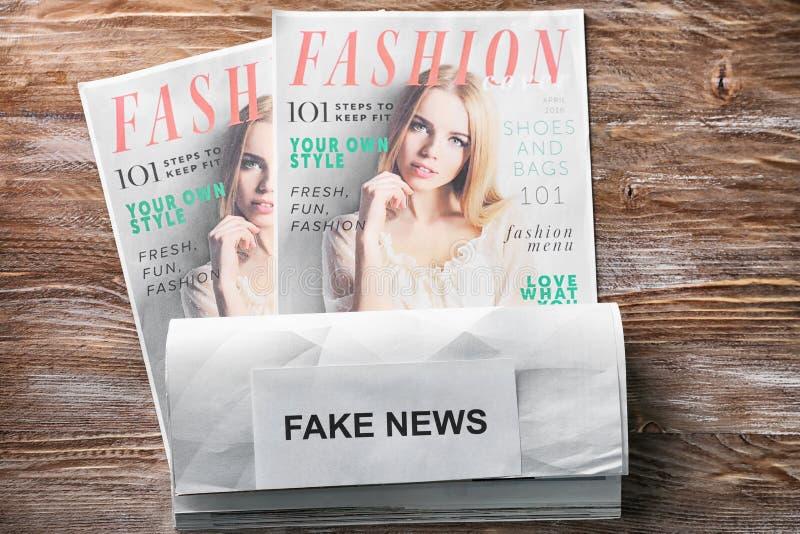 Papel con NOTICIAS FALSAS de la frase y revistas de moda en fondo de madera imagen de archivo