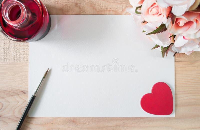 Papel da aquarela do espaço de trabalho ou papel de nota com tinta vermelha, coração vermelho, escova e ramalhete das rosas na ta fotos de stock