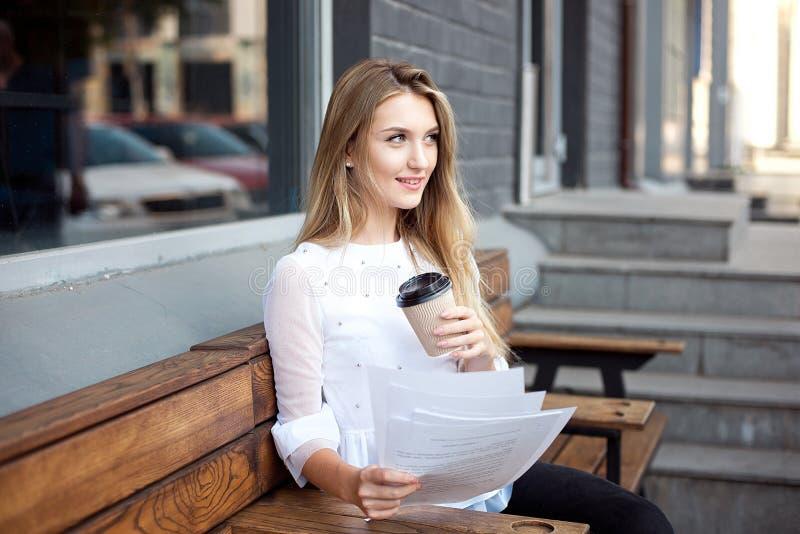 Papel da leitura da mulher de negócios no café durante a pausa para o almoço A mulher de negócio lê e sublinha notas em um contra imagens de stock