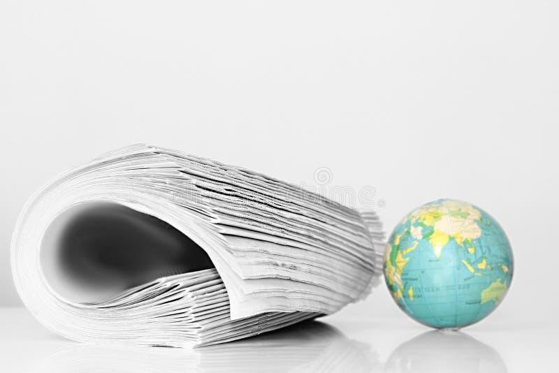 Papel da notícia com globo em uma tabela fotos de stock royalty free