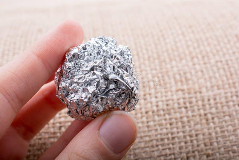 Papel de aluminio en la forma de una esfera en fondo texturizado imagenes de archivo