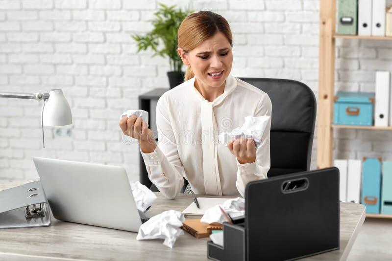Papel de amarrotamento forçado da mulher no local de trabalho foto de stock
