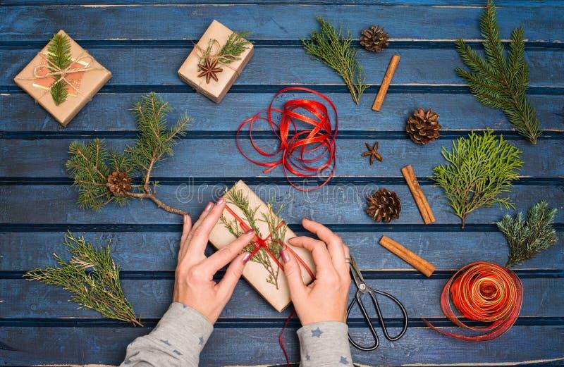 Papel de embrulho Caixas de empacotamento do presente de Natal Topview das mãos com árvore de abeto, cedro, zimbro, ramos Prepara foto de stock