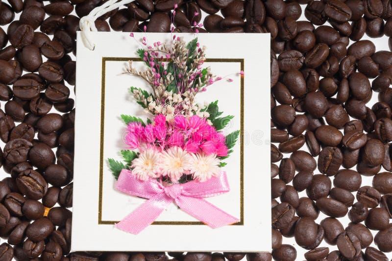 Papel de la postal con el fondo del grano de café de la flor fresca fotografía de archivo libre de regalías