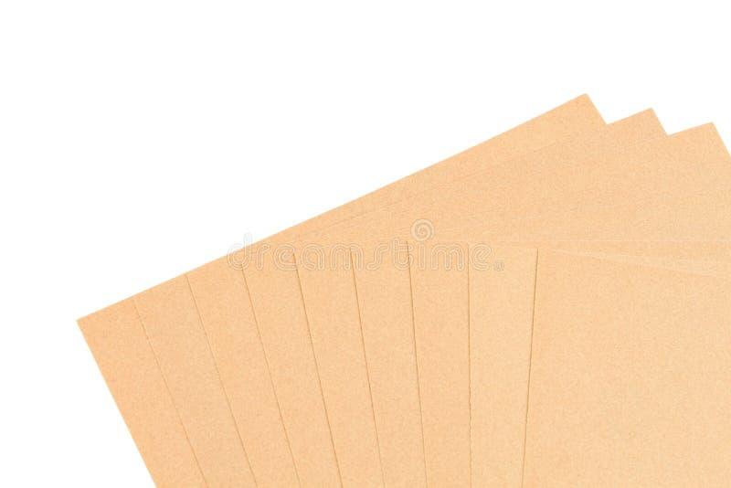 Papel de lija de la hoja de Brown para el trabajo de madera apilado aislado en los vagos blancos foto de archivo libre de regalías