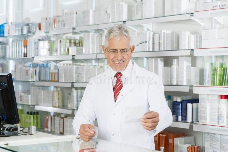 Papel de Looking At Prescription do químico no contador imagens de stock
