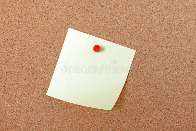 Papel de nota amarelo anexado com pino vermelho.