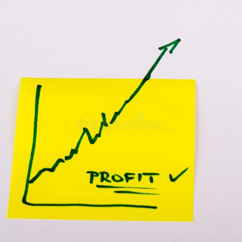 Papel de nota com o gráfico de negócio da finança que vai acima - lucro fotografia de stock royalty free