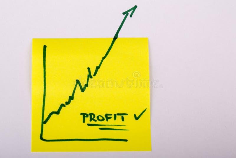 Papel de nota com o gráfico de negócio da finança que vai acima - lucro imagens de stock