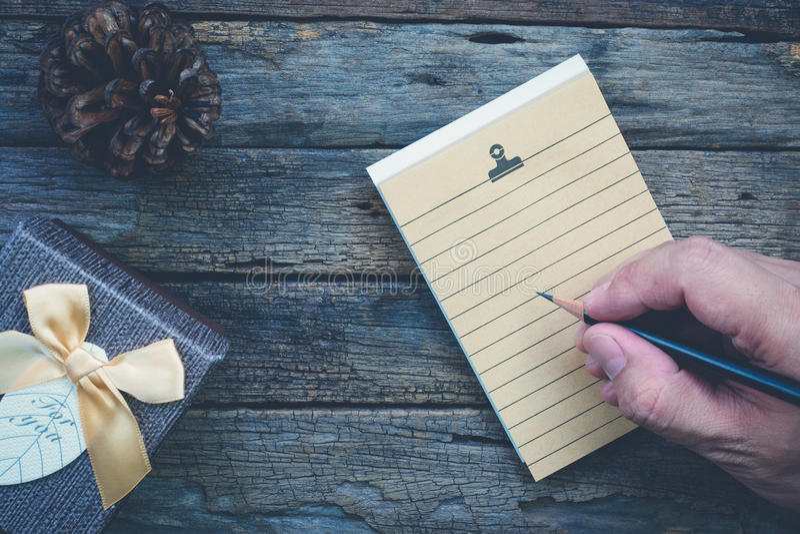 Papel de nota da página vazia, caixa atual, semente de pinho com mão e penc foto de stock
