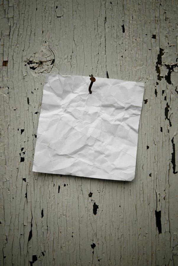 Papel de nota rasgado sucio clavado en viejo fondo resistido rústico imagenes de archivo