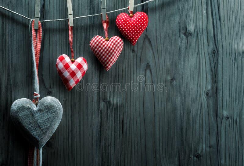 Papel de parede do dia de Valentim - corações de matéria têxtil que penduram na ordem de ascensão da corda imagem de stock royalty free
