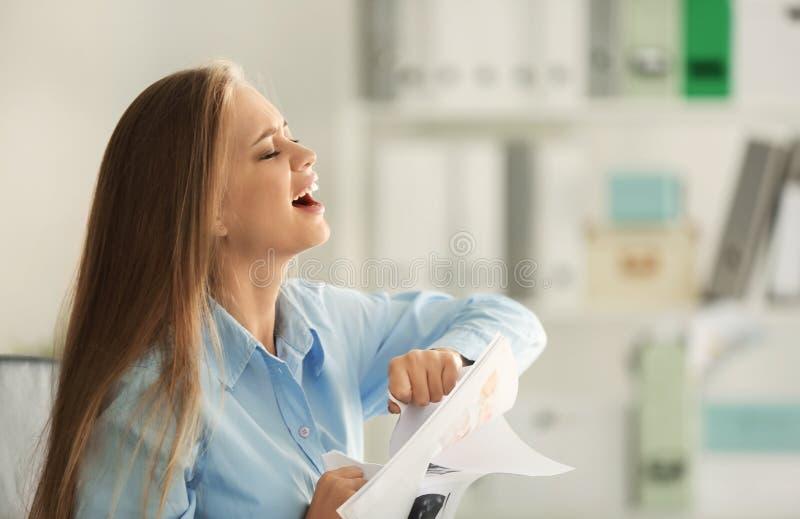 Papel de rasgo forçado da jovem mulher no local de trabalho fotos de stock royalty free