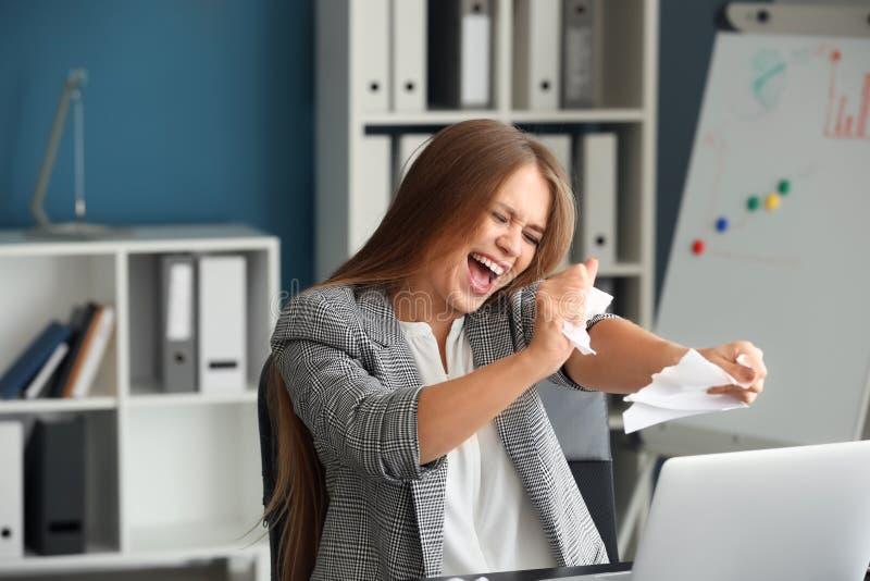 Papel de rasgo forçado da mulher no escritório imagem de stock royalty free