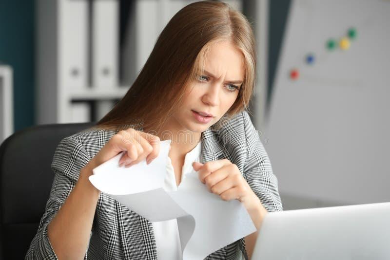 Papel de rasgo forçado da mulher no escritório imagens de stock