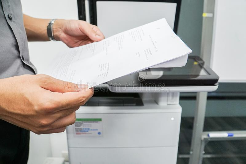 Papel del control del hombre de negocios para explorar en la impresora de oficina fotos de archivo libres de regalías