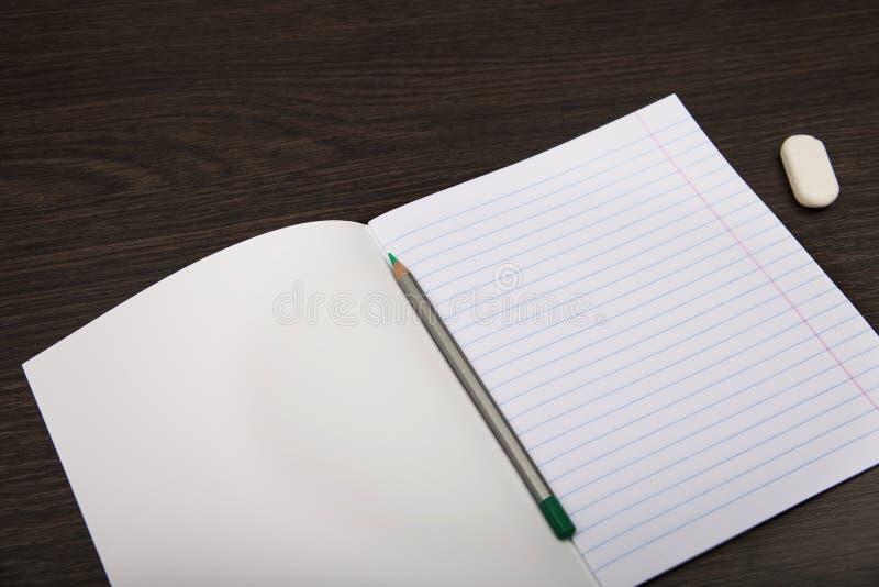 Papel do caderno da escola Caderno na linha e no l?pis caderno aberto em um fundo marrom planeamento stationery fotografia de stock royalty free