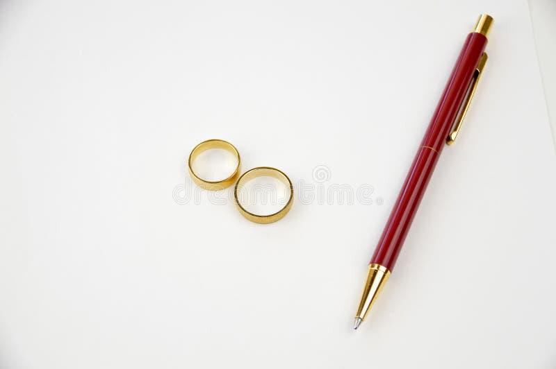 Papel do divórcio com alianças de casamento imagens de stock royalty free