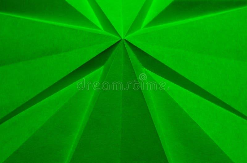 Papel dobrado cruciforme verde como o fundo abstrato do Natal fotografia de stock