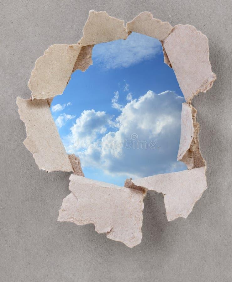 Papel e céu rasgados ilustração do vetor