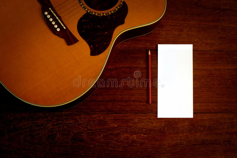 Papel e lápis de nota com guitarra acústica imagem de stock royalty free