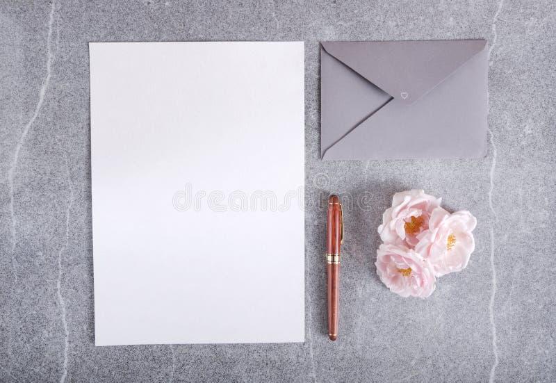 Papel en blanco para el texto, sobre y pluma, rosas rosadas en la superficie gris, visión superior imágenes de archivo libres de regalías