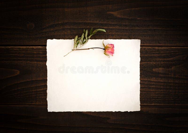 Papel esbranquiçado do vintage com a rosa secada consideravelmente cor-de-rosa na tabela de madeira escura do fundo da placa O pa fotos de stock royalty free
