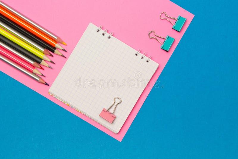 papel Escuela y materiales de oficina en un fondo coloreado azul y rosado Foco selectivo Espacio de publicidad imagen de archivo libre de regalías