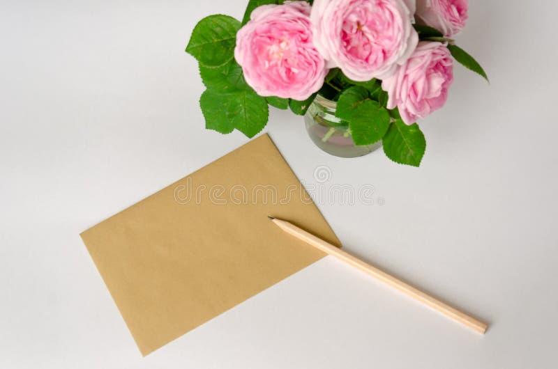 Papel hecho a mano marr?n de la hoja en blanco para el texto de saludo, un l?piz y las rosas rosadas en el fondo blanco Copie el  fotografía de archivo libre de regalías