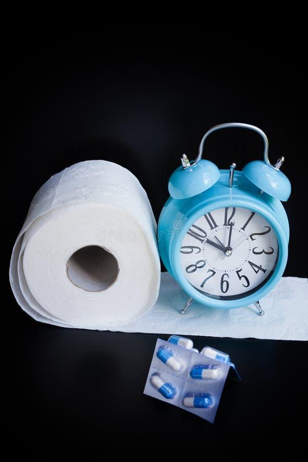 Papel higiênico, cápsulas e despertador no fundo preto fotos de stock royalty free
