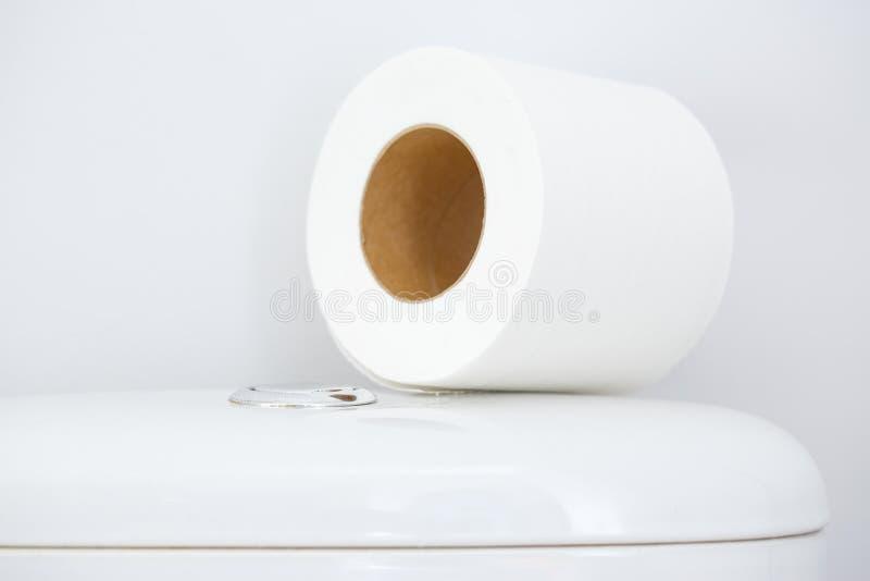 Papel higiênico no tanque branco do toalete imagem de stock royalty free